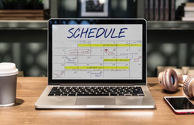 A laptop that shows a calendar scheduler