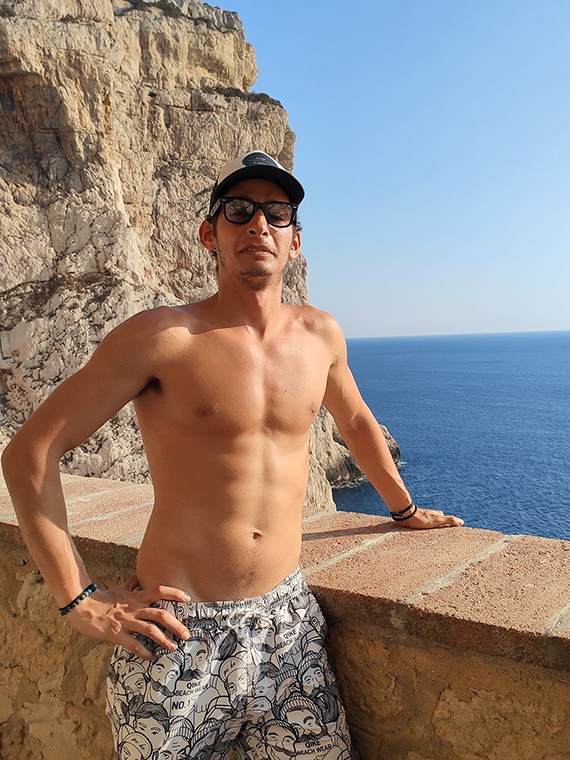 A monkmode person in a swimming suit wearing glasses with the ocean as a background