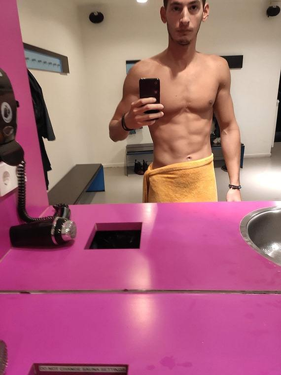 A half naked person in monkmode taking a picture in front of the mirror