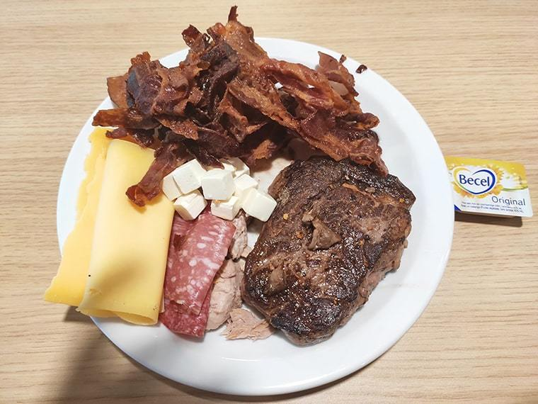 A monk mode plate that has cheese, steak, bacon, tuna, ham and butter on it.