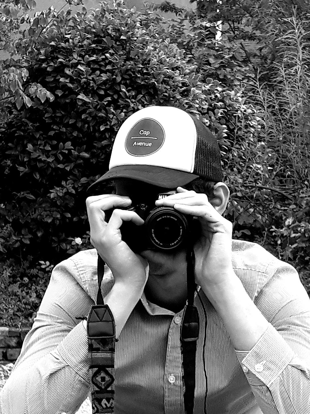 A person taking a photo and wearing a cap